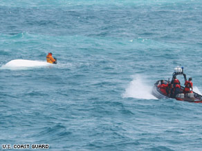 Photo Of Nick Schuyler Hanging On To Boat While Coast Guard Rescuses Him.  Photo: U.S. Coast Guard
